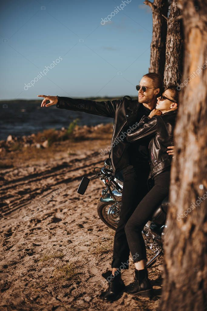man hugging girlfriend and pointing at seashore