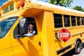 Fotografie usmívající se řidič zralé afroamerické autobusu při pohledu z okna a ukázal