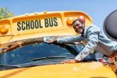 usmívající se řidič zralé afroamerické autobusu utírala předního okna školní autobus a při pohledu na fotoaparát