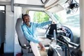 Fotografie usmívající se řidič zralé afroamerické autobusu při sezení uvnitř autobusu při pohledu na fotoaparát