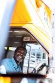 Fotografie řidič šťastný zralé afroamerické autobusu při pohledu na fotoaparát