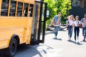 Skupina teenagerů učenců běží do školní autobus po lekcích se dostat domů
