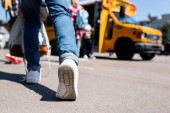 Fotografie cropped shot of student walking at school bus with classmates