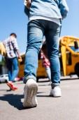 Fotografia ritagliata colpo dello scolaro a piedi a scuola bus con compagni di classe