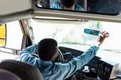 mature african american driver adjusting back view mirror at bus