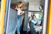 Teen školačka sjezdové školní autobus, zatímco starší řidič s úsměvem jí