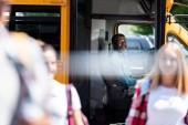 Fotografie Happy zralé školního autobusu řidič při pohledu na mládež na popředí