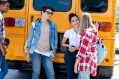 Skupina teenagerů učenců rozhovor a zároveň opírá se o školní autobus