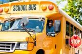 Fotografie pěkný starší školního autobusu řidič při pohledu na fotoaparát oknem