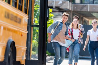 group of happy teen scholars running to school bus after lessons to get home