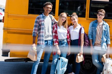 group of teen smiling scholars looking at camera while standing in front of school bus