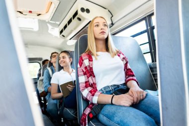 group of teen scholars riding school bus together