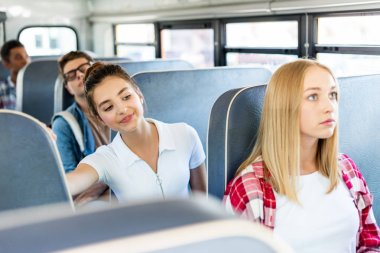 happy teen schoolgirl riding school bus with classmates and looking forward on road