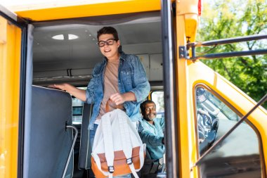 happy teen schoolboy walking out of school bus while driver looking at him