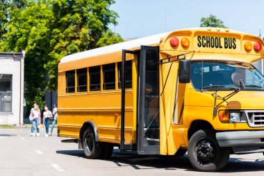 school bus standing on parking with blurred students walking on background