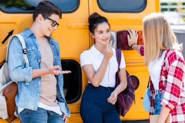teen students chatting while leaning on school bus