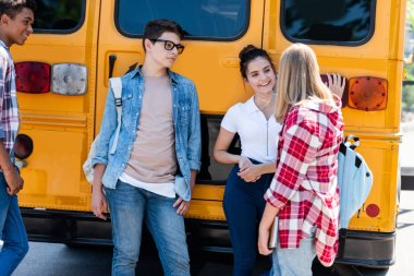 group of teen scholars talking while leaning on school bus