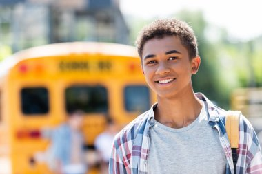 happy teen african american schoolboy looking at camera with blurred school bus on background