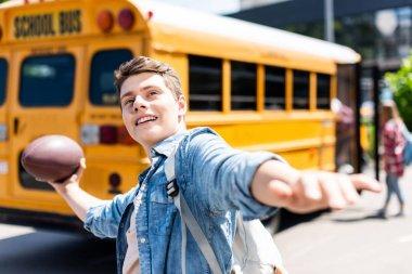 happy teen schoolboy throwing american football ball in front of school bus