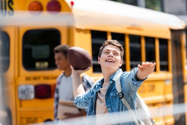 happy teen schoolboy throwing american football ball in front of school bus with blurred classmate walking on background