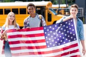 Fotografie group of happy teen students holding usa flag in front of school bus