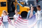 csoport amerikai tini tudós urai usa zászló előtt iskolabusz
