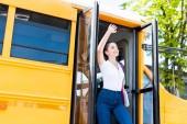 Fotografie happy teen schoolgirl walking out school bus and waving