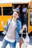 Fotografie celebrating teen schoolboy running out of school bus with blurred classmates on background