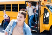 Fotografie group of happy teen scholars running out school bus