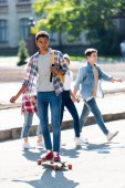 handsome young african american schoolboy riding skateboard with blurred classmates walking on background