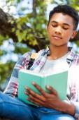 Fotografie pohled zdola zaměřené teen student čtení knihy pod stromeček