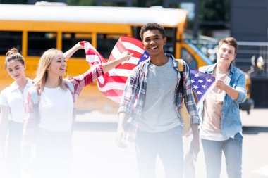 group of multiethnic american teen scholars walking with usa flag in front of school bus