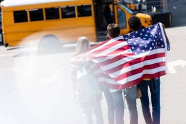 Rear view of group of american teen scholars with usa flag in front of school bus stock vector