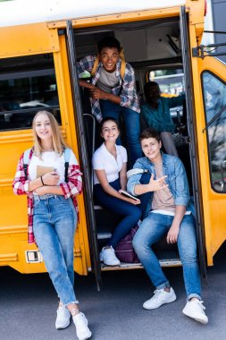 group of smiling teen scholars sitting at school bus with driver inside and looking at camera