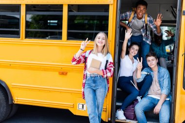 group of teen scholars sitting at school bus with driver inside and showing various gestures at camera