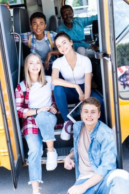 group of teen scholars sitting at school bus with driver inside and looking at camera