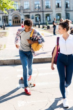 teen students walking at college garden with skateboard