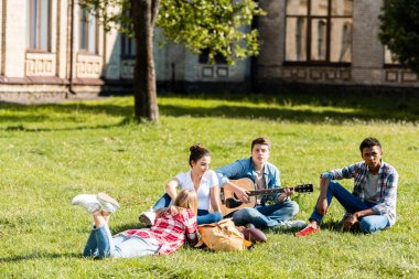 group of teenagers spending time together and listening to guitar song on grass
