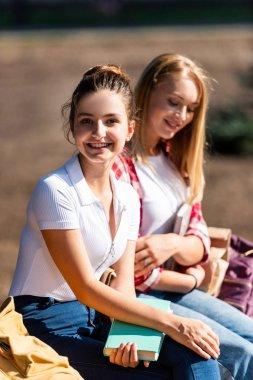 Happy teen schoolgirls sitting on bench with books stock vector