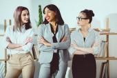 mosolygó többnemzetiségű üzletasszonyok formális viselni állt keresztbe