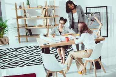 Smiling young businesswomen working with blueprints in modern office