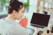 mladá Asiatka Návrhář pití kávy při práci s grafickým tabletem a notebookem