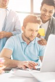focused young businessman using laptop and colleagues standing behind in office