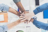 Close-up partial view of businessmen stacking hands while working on project together, business teamwork concept