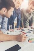 drei junge Geschäftsleute lehnen sich an einen Tisch und arbeiten gemeinsam an einem Projekt, unternehmerisches Teamwork-Konzept