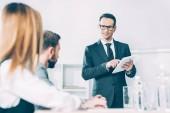 podnikatel s tabletem, mluvit s partnery v konferenčním sále