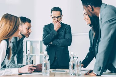 multiethnic successful businesspeople having conversation in conference hall