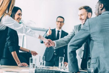 multicultural businesspeople shaking hands in conference hall while team leader showing thumb up