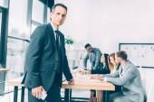 pohledný podnikatel v oblek stál v konferenční sál s mnohonárodnostní kolegy konverzaci