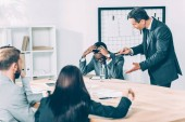 Photo caucasian boss abusing on african american manager in conference hall with his colleagues